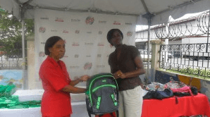 Rubis Retail Accounts Executive Rhonda Johnson handing over a haversack to a representative from the children's homes